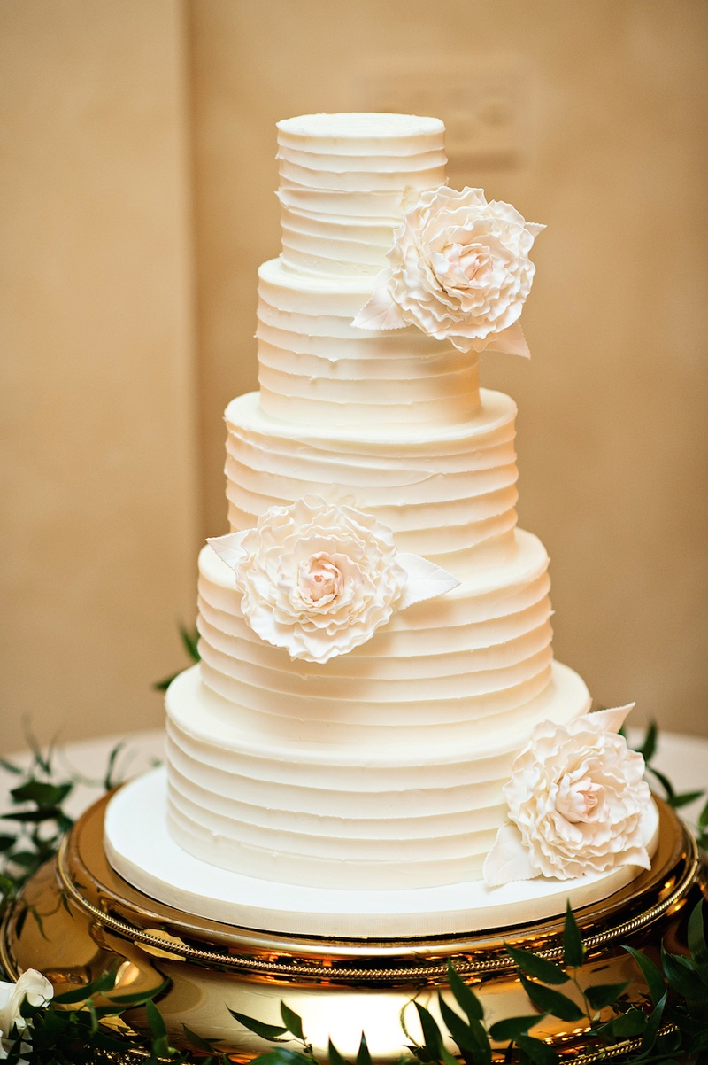 White wedding cake with textured frosting and white sugar peonies