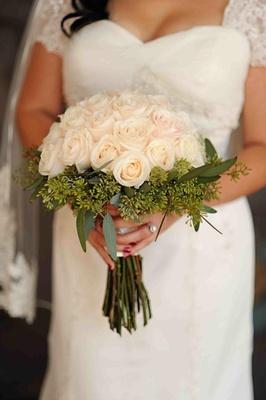 Bride in vintage-inspired wedding dress holding roses
