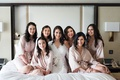 bride in lace trim white robe getting ready photo with bridesmaids and flower girls
