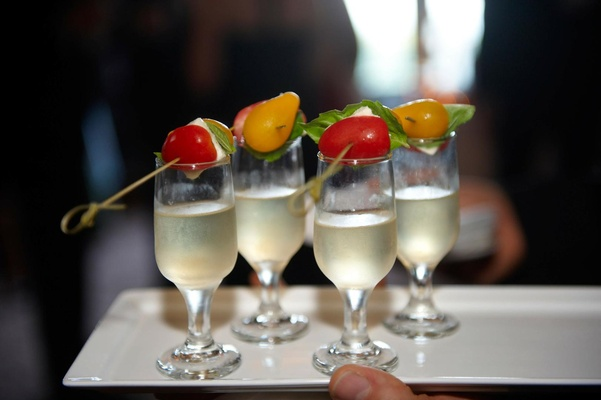 Glasses of Champagne are served with caprese salad hors d'oeuvres at wedding cocktail hour