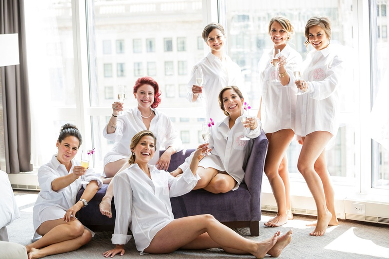 Bride and bridesmaids toast drinks with flower garnishes in bridal suite high rise
