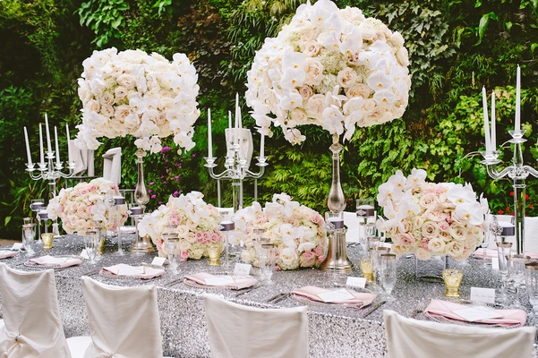 Silver sequin tablecloths with white ruffle chair covers and tall ivory flower arrangements