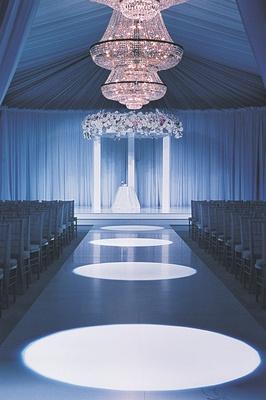 Opulent indoor wedding ceremony with chandelier and drapery