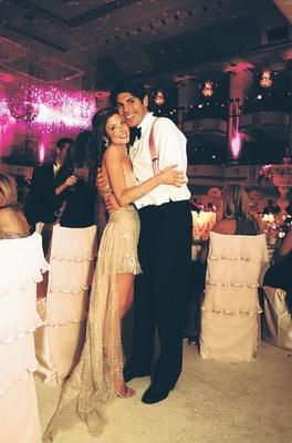 Groom hugs bride wearing short tan dress at reception