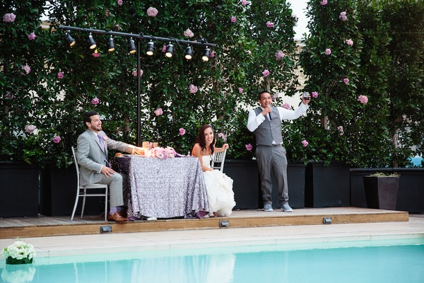 Best man in grey vest and pants, white shirt, gives poolside toast to newlyweds