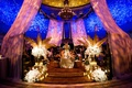 Wedding reception drapery with bright lights pink blue drapery gold palm leaves white flowers guests