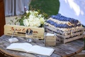 Ranch wedding reception with wood crate of beige and purple scarf blanket on rustic wood table