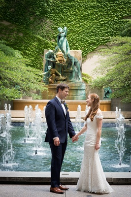 Wedding portrait bride and groom holding hand by fountain romona keveza wedding dress brown shoes