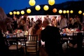 Bride and groom kiss at night reception with yellow lanterns
