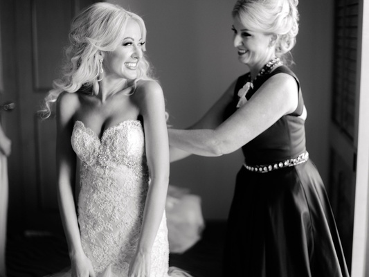 Black and white photo of bride smiling in strapless wedding dress at mom helping her button the back