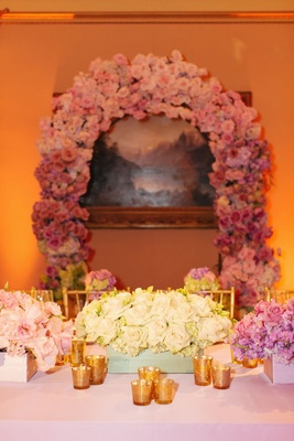single-variety bouquets in low boxes and pink ombre arch on wall