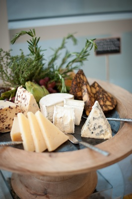 Blue cheese, brie cheese, and others on wood stand
