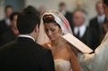 Bride and groom at ceremony in front of Catholic priest