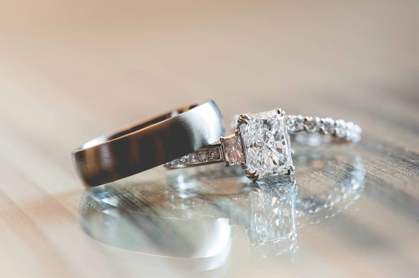 Three stone emerald cut engagement ring with grooms brushed finished band and bride's diamond band