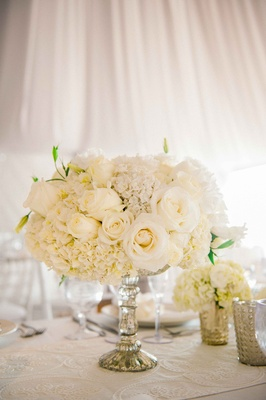 Beach tented wedding reception table with embroidered runner, ivory roses, hydrangeas in silver