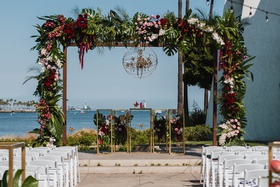 unique chandelier in sphere display, large wedding arbor chuppah with tropical leaves