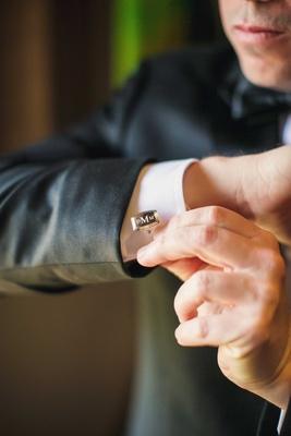 Groom getting ready for wedding day putting on monogram three initial cufflink