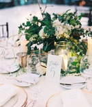 wedding reception centerpiece greenery white flowers calligraphy table number gold terrarium candles