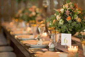 Wedding reception long wood table with lace napkin details gold rim goblet table number low flowers