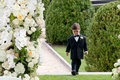 Ring bearer in a black tuxedo and bow tie