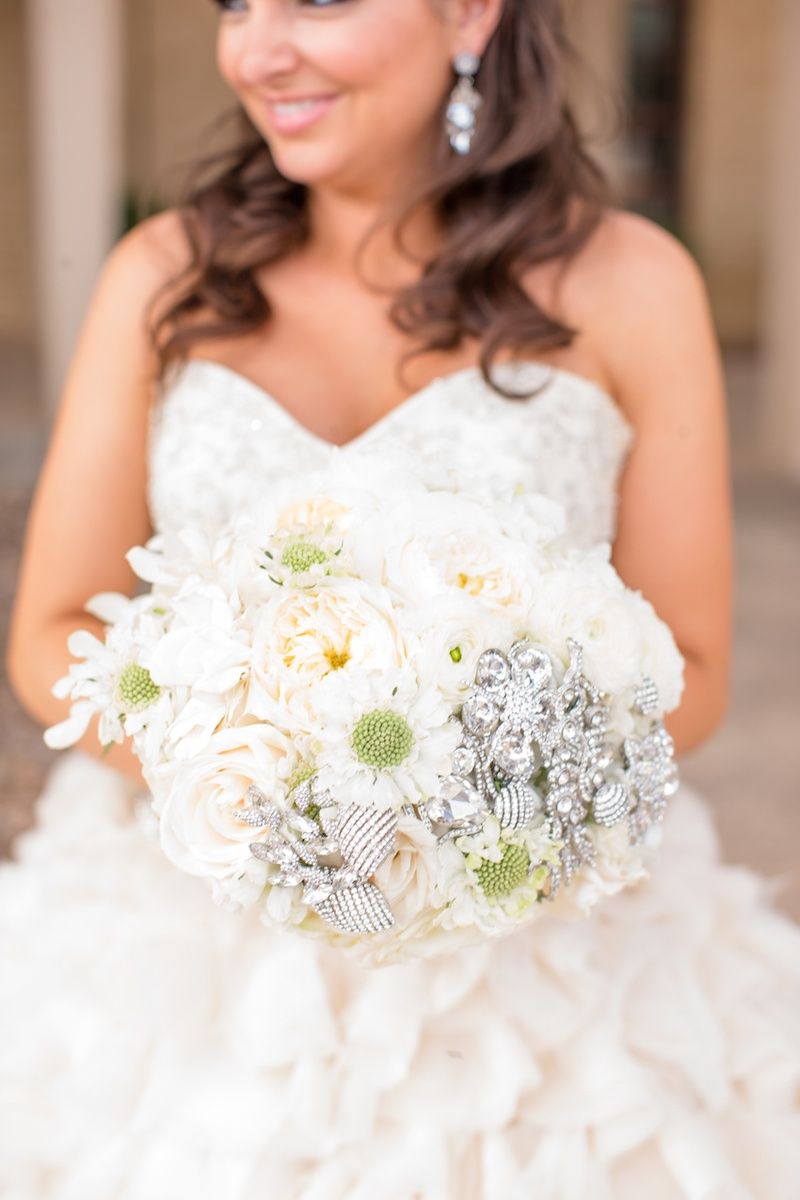 jeweled ivory wedding bouquet jeweled wedding dress Bride in ruffle wedding dress holding white bouquet with brooches