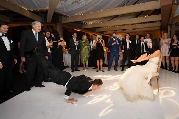 groom does the worm to his bride for the garter toss