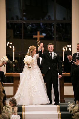 bride in isabelle armstrong lace gown, groom in tuxedo, arms raised in celebration