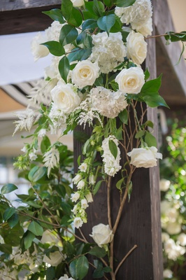 varying white flowers and green foliage winding up a wooden chuppah at a couples Jewish ceremony