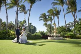 bride in purple floral romona keveža wedding dress, groom in navy tuxedo, palm trees