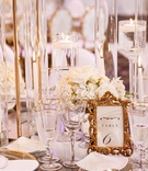 wedding reception table gold flatware and charger plate white flowers gold rim glassware tall riser