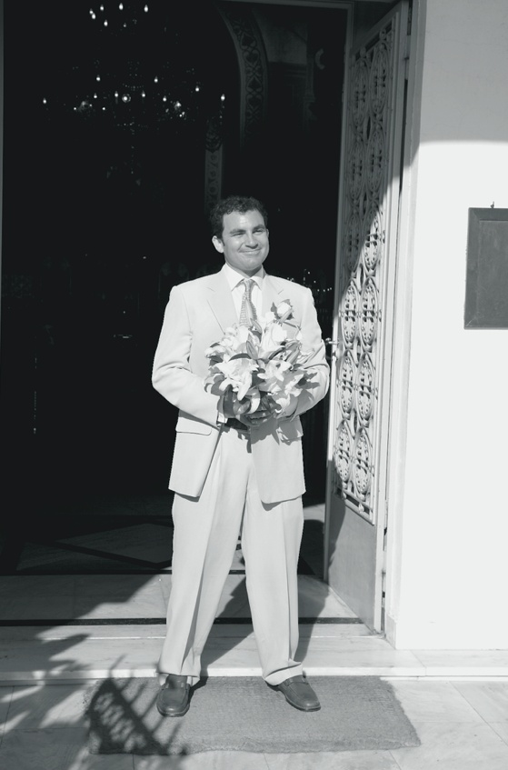 Black and white photo of groom with flowers