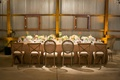 Tin barn wedding reception head table with rustic chairs