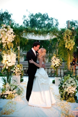Bride and groom eskimo kiss under green and white flower arch