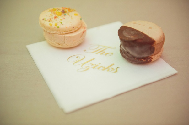 Sprinkled macaron and chocolate dipped macaron ice cream sandwiches on personalized napkin