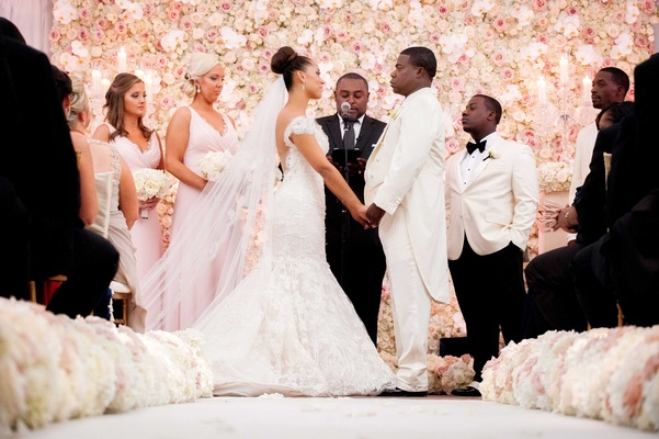 Wedding ceremony of Megan Wollover and Tracy Morgan in front of pink flower wall in New Jersey
