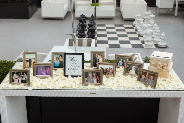 wedding ceremony memorial table with photos and ivory rose petals