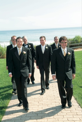 Men in black tuxedos walking away from beach
