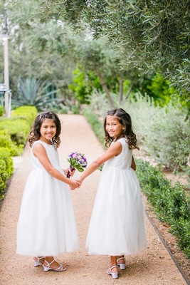 flower girls in white dresses with pink and purple bouquets hold hands in arizona