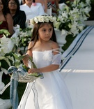 Pretty flower girl walking down white and blue aisle