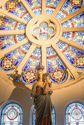 Statue and stained glass window in circle shape at Chicago church ceremony