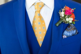 pink and orange boutonniere with blue suit and yellow tie