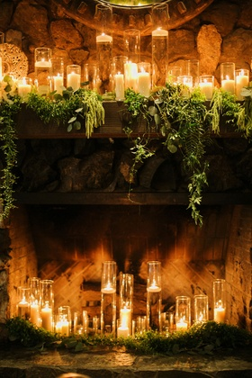 fireplace full of candles, candles on mantle with greenery