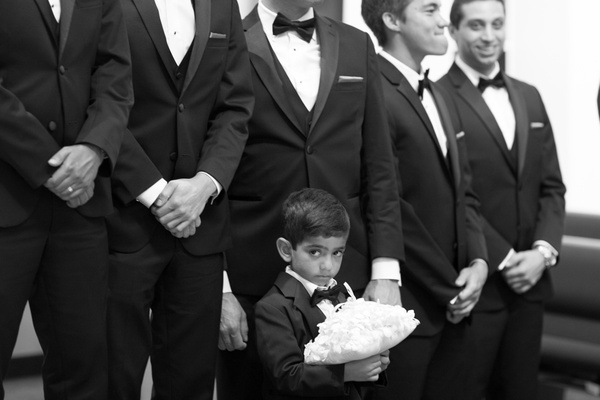 Black and white photo of young ring bearer in tux standing in front of groomsmen