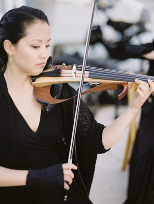 Woman playing electric violin modern looking instrument at wedding ceremony outdoors levine toilolo