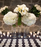 Wedding reception tall glass vases filled with hydrangea, calla lily rose flowers hexagon marble