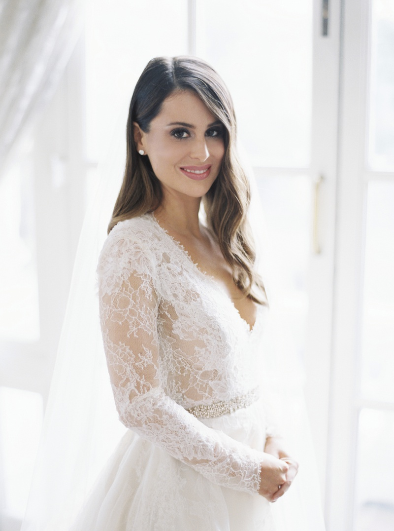 bride in monique lhuillier lace long sleeve a-line gown, brunette hair in soft waves, natural makeup