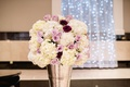White hydrangea and purple rose flower arrangement in silver vase at wedding ceremony string lights