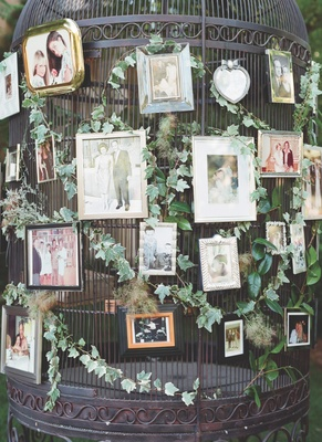 Family photos displayed on a large birdcage for a wedding