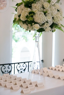 Wedding reception white table with tall glass vase ivory hydrangea rose ferns greenery escort cards