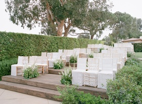 Outdoor ceremony on wood deck with white lace chair covers